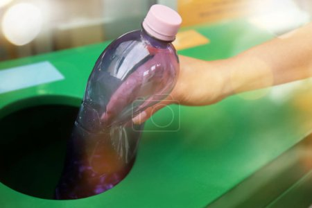 Woman throwing plastic bottle into litter bin, closeup. Recycling concept