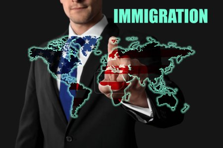 Word IMMIGRATION, man pushing button with American flag and world map on virtual screen against dark background