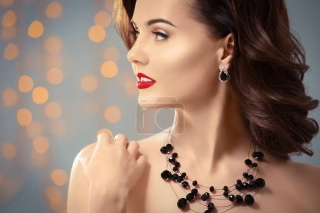 Portrait of beautiful young woman with luxury jewelry on blurred background