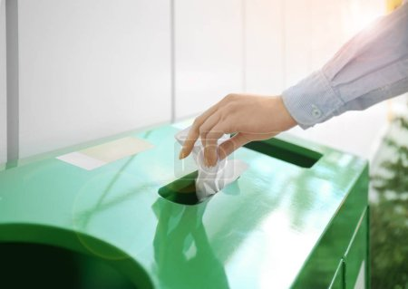Woman throwing paper into litter bin, closeup. Recycling concept