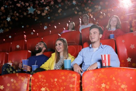 Young people watching movie in cinema. Frame of blurred lights