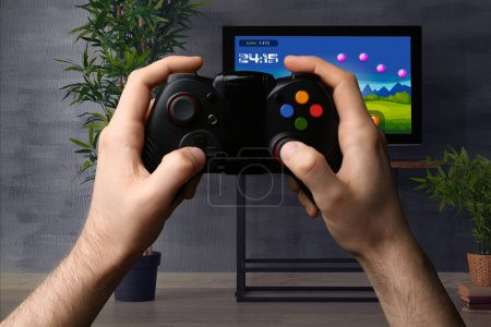 Man with controller playing video game at home. Leisure and entertainment
