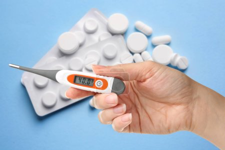 Woman holding thermometer with high temperature and pills on background