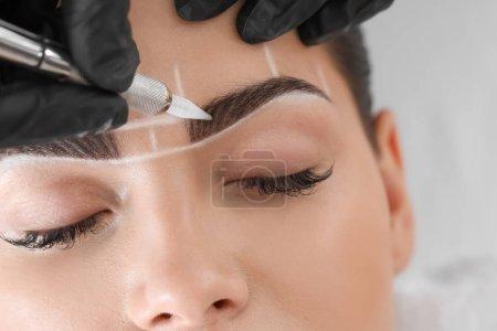 Photo pour Jeune femme subissant une procédure de maquillage permanent des sourcils dans un salon de beauté, gros plan - image libre de droit