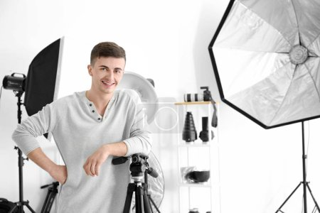 Photo pour Jeune homme posant pour photographe professionnel en studio - image libre de droit