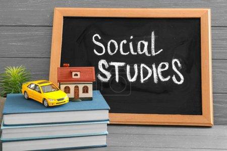"""Photo pour Tableau avec l'expression """"études sociales"""", voiture jouet et maison sur la table - image libre de droit"""