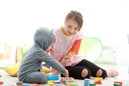 Petite fille mignonne avec jeune nounou à table, à l'intérieur