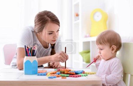 Photo pour Jolie petite fille avec jeune nounou à table, à l'intérieur - image libre de droit