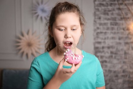 Photo for Overweight girl eating doughnut indoors - Royalty Free Image