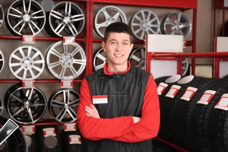 Young mechanic in store with tires and alloy wheels