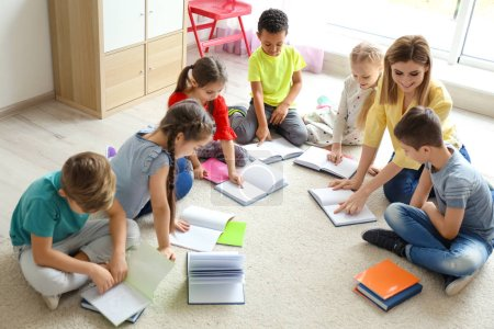 Female teacher helping children with homework in classroom at school