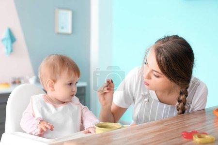 Photo pour Jeune nounou mignonne petite fille, à l'intérieur de l'alimentation - image libre de droit