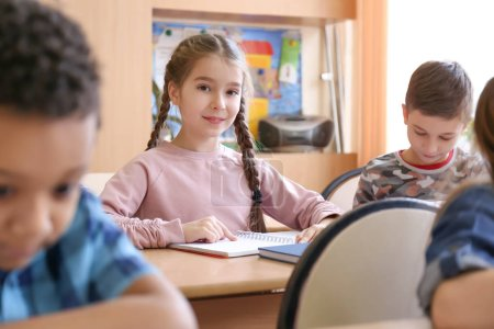 Photo for Female teacher helping children with homework in classroom at school - Royalty Free Image