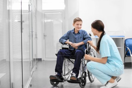 Young female doctor taking care of man in wheelchair indoors