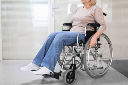 Mature woman sitting in wheelchair indoors