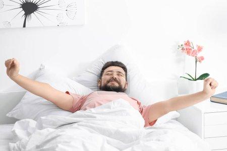 Foto de Mañana del hombre que estira en la cama en casa - Imagen libre de derechos