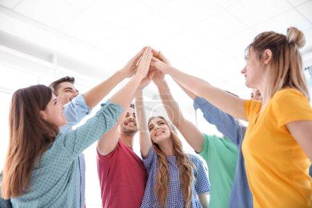 Photo pour Les jeunes mettent les mains ensemble sur un fond clair. Concept d'unité - image libre de droit