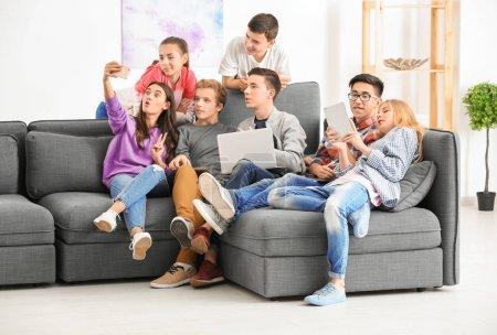 Foto de Grupo de adolescentes con los dispositivos modernos tomando selfie sentado en el sofá en el interior - Imagen libre de derechos