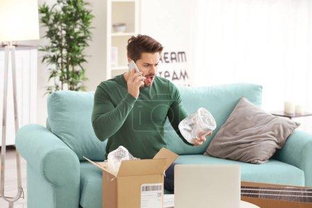 Photo pour Jeune homme passer un appel au sujet du colis livré à la maison - image libre de droit