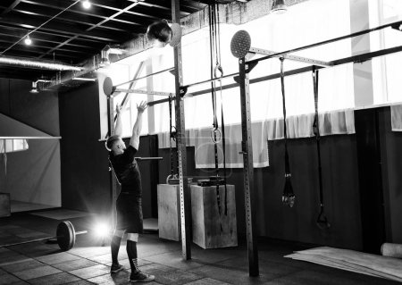 Photo for Muscular man doing exercise with medicine ball in gym.  Young man doing upper body exercise working out with heavy weighted ball - Royalty Free Image