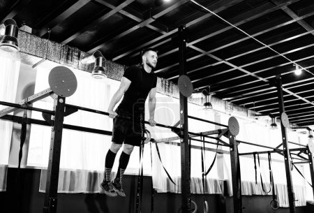 Young man exercising on horizontal bar in the gym. Male adult working out triceps and biceps on horizontal bar