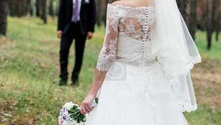Photo for Beautiful bride in wedding dress with wedding bouquet of peonies waiting for the groom in the park outdoors before wedding ceremony - Royalty Free Image