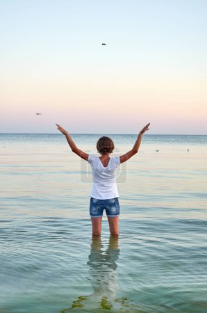 Beautiful young woman standing in water, raising her hands up and flying as seagull on the sea. Girl enjoying freedom and fresh air on ocean beach, copy space