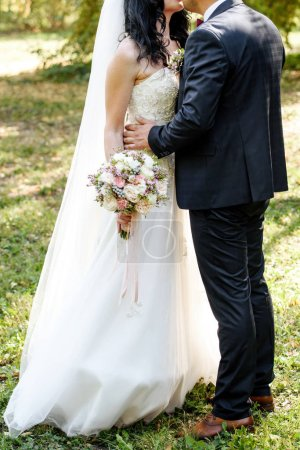 Happy bride and groom hugging and kissing on wedding ceremony outdoors, copy space. Wedding couple in love, newlyweds. Wedding concept, bridal bouquet
