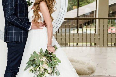 Photo pour Joyeux marié et mariée câlins lors de la cérémonie de mariage à l'intérieur, copier l'espace. Couple amoureux, jeunes mariés. Groom tenant la taille de la mariée. Concept de mariage - image libre de droit