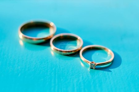 Three wedding rings on turquoise wooden background, selective focus. Engagement ring with diamond, bridal ring and groom ring, free space. Accessories for wedding day. Proposal and wedding concept