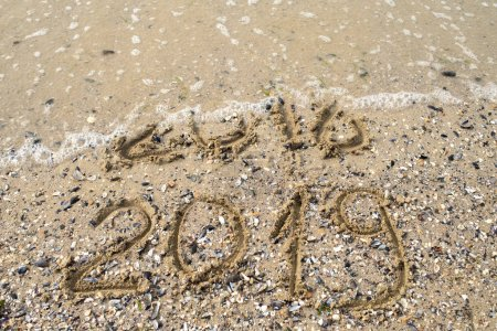 Photo for New Year 2019 replace 2018 on the sea beach concept, copy space. Wave starting to cover digits 2018. New Year 2019 is coming concept - Royalty Free Image