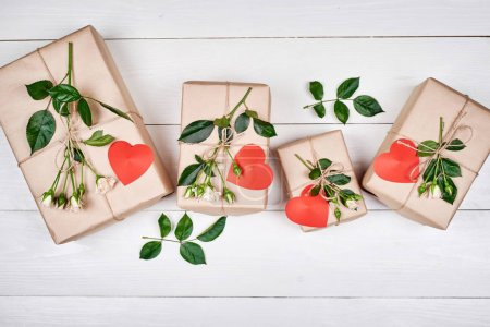 Photo for Gift boxes with fresh rose flowers and red hearts on wooden desk, copy space. Holiday background, sale, shopping. Gift wrapping. Valentines Day, Womens Day, Mothers Day. Top view, flat lay - Royalty Free Image