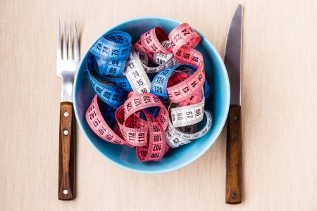 Diet food healthy lifestyle and slim body concept. Many colorful measuring tapes in blue bowl on table with knife and fork, top view