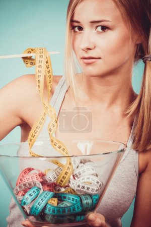 Diet, healthy food, weight loss and slim body concept. Fit fitness girl holding bowl eating colorful measuring tapes