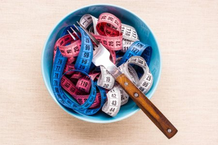 Diet food healthy lifestyle and slim body concept. Many colorful measuring tapes in blue bowl on table with fork, top view