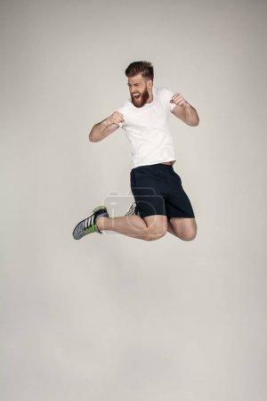 Photo pour Un bel athlète barbu a sauté sur la colline en studio. portant des baskets et un T-shirt blanc. face au mur blanc . - image libre de droit