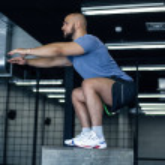 Man doing squats on a squat box at the gym. guy at...