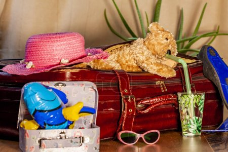 Travel concept of Teddy bear and red vintage suitcase