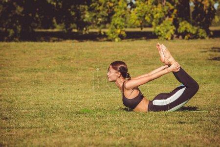 woman practicing yoga in park, Dhanurasana pose