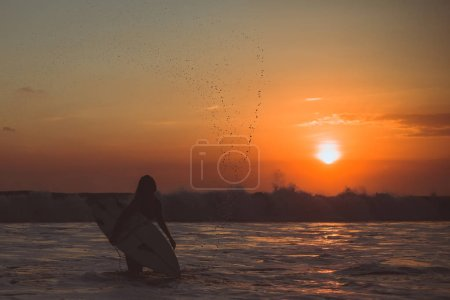 Photo for Surfer woman silhouette with surfboard in sea, sunset reflection in water and splashes water drops - Royalty Free Image