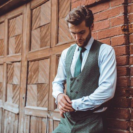 Photo pour Bel homme caucasien en costume gilet posant au mur de construction de briques et ajustant la manche, la mode masculine - image libre de droit