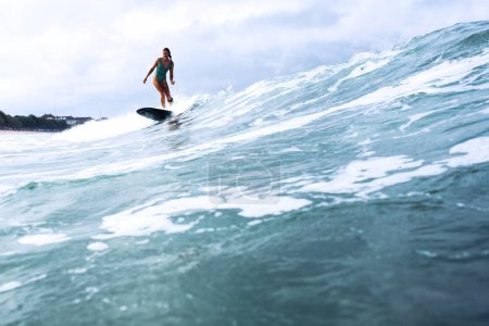 Photo for Beautiful surfer girl riding on a board in the ocean on bali island - Royalty Free Image
