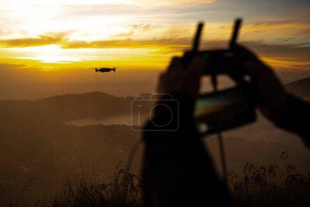 Photo pour Vue rapprochée de l'homme contrôlant le drone sur le volcan Batur au coucher du soleil. Bali, Indonésie - image libre de droit