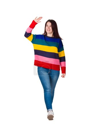 Full length portrait of carefree friendly young woman, smiling broadly while waving palm raised up, greeting friend, say hello gesture. Casual girl wearing jeans and sweater isolated over white.
