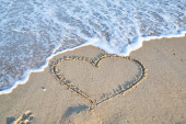 Love message on the beach sand - vacation and travel concep