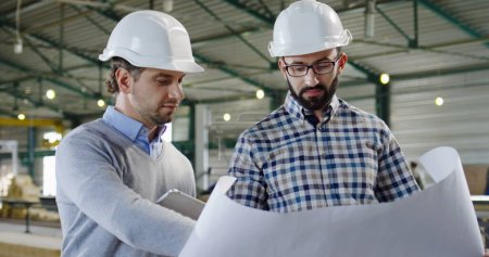 Photo for Two Caucasian handsome men in helmets talking and looking at the big paper with drawings and discussing it. Factory space. Indoor. Portrait. Close up - Royalty Free Image