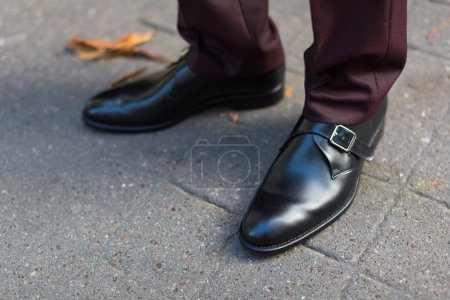 Photo for Male feet in elegant leather shoes standing on asphalt outdoors - Royalty Free Image