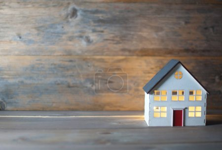 Photo for Model house with lights on inside over a wooden background - Royalty Free Image