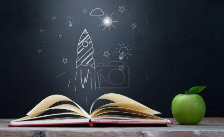 Photo pour Esquisse de fusée émergeant d'un livre ouvert - image libre de droit