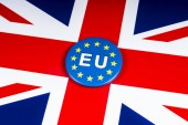 London, UK - November 20th 2018: An EU pin badge, pictured over the flag of the United Kingdom.